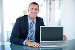 Businessman showing laptop. In his office royalty free stock images