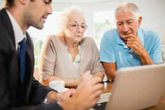 Businessman showing laptop to senior couple. At home stock photos