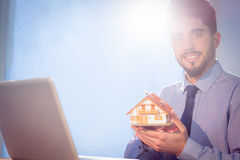 Businessman showing a mini house. Shot in studio royalty free stock image