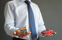 Businessman showing models of a house and a car Stock Image