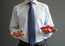 Businessman showing models of a house and a car Royalty Free Stock Photos