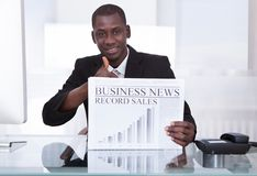 Businessman Showing Newspaper Stock Photo