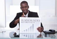 Businessman Showing Newspaper Stock Photo