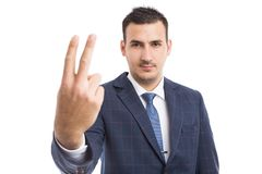 Businessman showing number two with fingers. Suited and isolated on white studio background Royalty Free Stock Photos