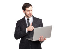 Businessman showing ok with a laptop. Businessman showing ok sign with a laptop in his hands royalty free stock photography