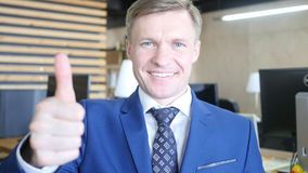 Businessman showing OK sign with his thumb up. Selective focus on face. High quality Stock Photo