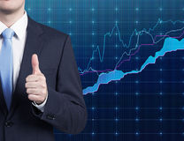 Businessman showing ok symbol. And drawing graphs on wall Royalty Free Stock Image