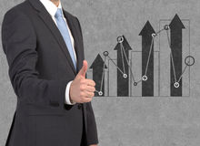 Businessman showing ok symbol. And drawing graphs on wall Royalty Free Stock Photo