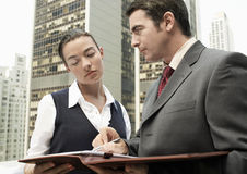 Businessman Showing Paperwork To Woman Outdoors Stock Image