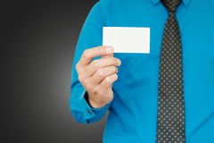 Businessman showing pasteboard. Closeup card in right hand of blue shirt businessman on gray background Royalty Free Stock Image