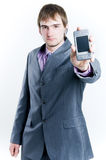 Businessman showing phone. Focus on phone, isolated on white background Royalty Free Stock Image