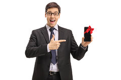 Businessman showing phone wrapped with red ribbon and pointing Royalty Free Stock Images