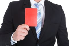 Businessman showing red card. Midsection of young businessman showing red card over white background Royalty Free Stock Photography