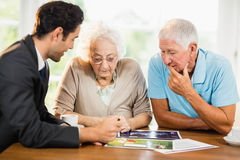 Businessman showing sheets to senior couple Royalty Free Stock Photography