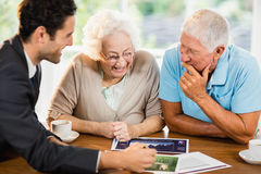 Businessman showing sheets to senior couple Royalty Free Stock Photo
