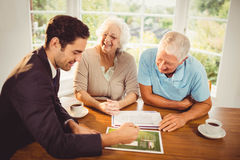 Businessman showing sheets to senior couple Royalty Free Stock Photos