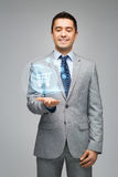 Businessman showing shopping trolley hologram Royalty Free Stock Photo