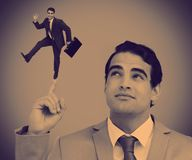 Businessman showing shrunk colleague posing on his finger Royalty Free Stock Image