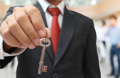 Businessman showing the silver key Royalty Free Stock Photos