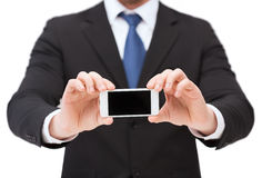 Businessman showing smartphone with blank screen Royalty Free Stock Images