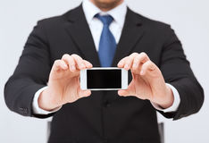 Businessman showing smartphone with blank screen Royalty Free Stock Photography