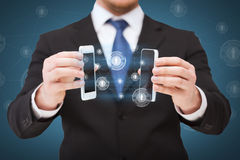 Businessman showing smartphones with blank screens. Business, internet and technology concept - businessman showing two smartphones with blank black screens Royalty Free Stock Photos