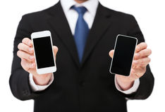 Businessman showing smartphones with blank screens. Business, internet and technology concept - businessman showing two smartphones with blank black screens Royalty Free Stock Image