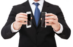 Businessman showing smartphones with blank screens Stock Photo