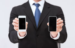 Businessman showing smartphones with blank screens. Business, internet and technology concept - businessman showing two smartphones with blank black screens Royalty Free Stock Photo