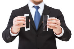 Businessman showing smartphones with blank screens Royalty Free Stock Image