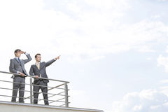 Businessman showing something to coworker against cloudy sky Royalty Free Stock Photos