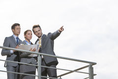 Businessman showing something to coworkers on terrace against sky Royalty Free Stock Image