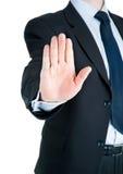 Businessman showing STOP sign. Black dressed businessman showing STOP Royalty Free Stock Photography