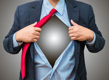 Businessman showing a superhero suit underneath his suit, isolat Stock Photography