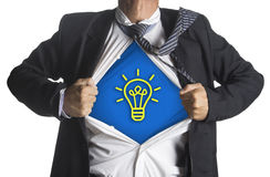 Businessman showing a superhero suit underneath idea light bulb Royalty Free Stock Photo