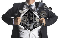 Businessman showing a superhero suit underneath machinery stock photography