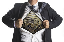 Businessman showing a superhero suit underneath machinery metal. Gears idea concept, isolated on white background Royalty Free Stock Images