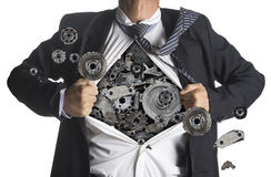 Businessman showing a superhero suit underneath machinery metal Stock Image