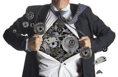 Businessman showing a superhero suit underneath machinery metal stock image