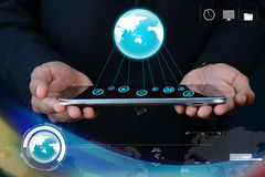 Businessman showing tablet with global networking Stock Photo