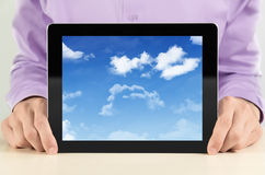 Businessman Showing Tablet PC With Cloudscape. Businessman showing digital tablet pc with cloudscape on screen. Concept image on a cloud-computing theme Royalty Free Stock Images