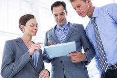 Businessman showing tablet to his colleagues Stock Photo