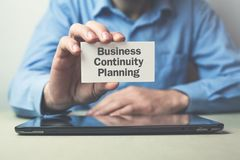 Businessman showing text Business Continuity Planning on business card. royalty free stock photography