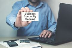 Businessman showing text Business Continuity Planning on business card. stock photo