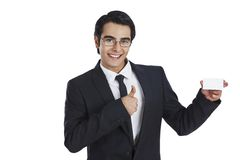 Businessman showing thumb sign and visiting card stock image