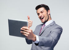 Businessman showing thumb up to tablet computer Stock Photos