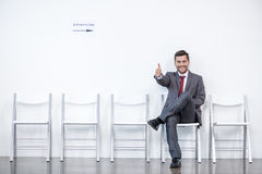 Businessman showing thumb up and waiting for interview in office. Business concept Stock Photos