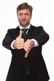 Businessman showing thumbs up and down. Picture of handsome bearded businessman showing thumbs up and down. Serious man expressing his negativity Royalty Free Stock Photos