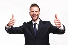Businessman showing thumbs up gesture. Studio portrait of young handsome businessman showing thumbs up gesture isolated on white background stock photography
