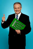 Businessman showing thumbs up, holding calculator Royalty Free Stock Photography